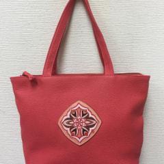 ワンポイントの朱色のバッグ